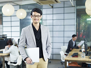 portrait of young asian entrepreneur standing in office smiling