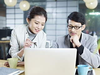 asian business man and woman working together using laptop in office