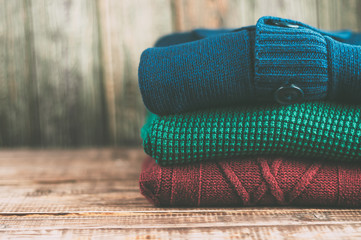 Warm clothes laid in a pile on wooden background.Colorful sweaters on a wooden table.