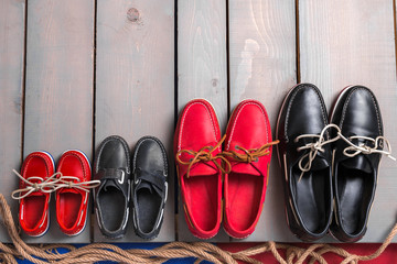 Family boat shoes on wooden background. Four pair of red and black boat shoes on grey desk with rope. Top view, copy space. family concept
