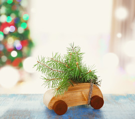 Toy car with fir tree branch