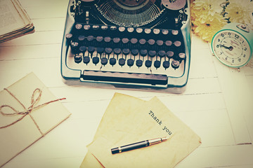 Vintage black typewriter with old books and flowers on wooden table
