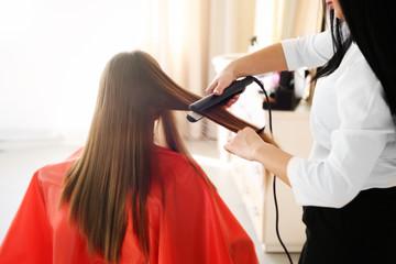 Professional hairdresser straightening hair