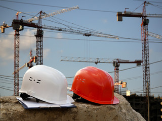 Building helmet on a background of cranes, construction