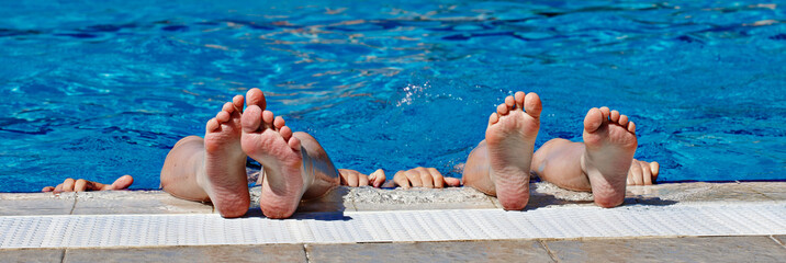 Children's feet in a spray of water in the pool