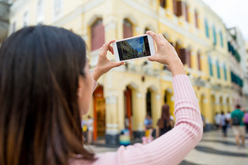 Woman taking photo by cellphone in Macau city