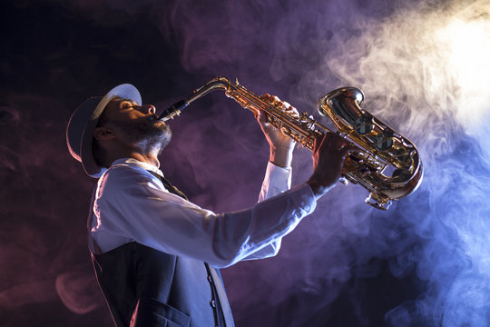 Saxofonista sobre escenario con humo