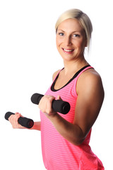 An attractive woman in a pink top standing against a white background doing barbell curls with weights. Smiling towards camera.
