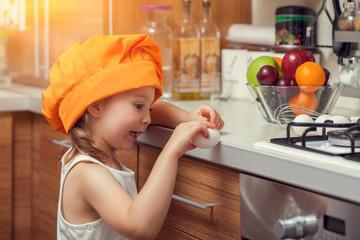 beautiful cute little girl with bonnet breaking an egg in kitchen
