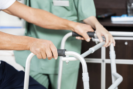 Patient's Hands Holding Walker By Nurse In Rehab Center