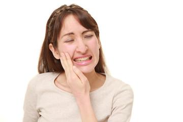激しい虫歯の痛みに苦しむアラサーの女性