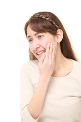 激しい虫歯の痛みに苛まれるアラサーの女性