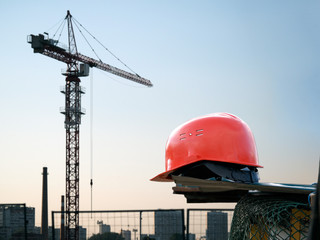 Orange construction helmet on a background of  crane,