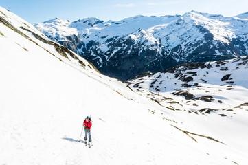 Female skier ascending a mountain slope.