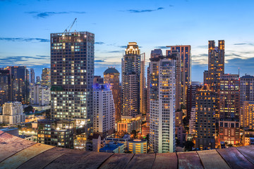 night light of Bangkok wooden floor. Panoramic and perspective view background of glass high rise building skyscraper commercial of future. Business concept of success industry tech architecture