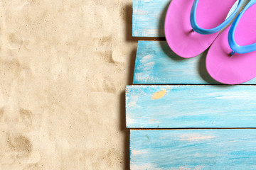 Pink flip flop on blue wooden boards on the sand beach