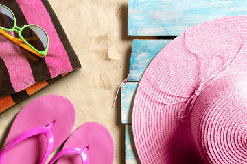 Summer beach accesories on blue wooden boards on the sand beach