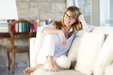 Perfect day at home. Smiling attractive woman relaxing while sitting in her living room at sofa.