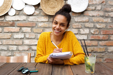Smiling young lady sitting at cafe with notepad