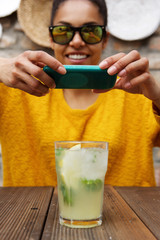 Woman taking picture of mojito with her mobile phone