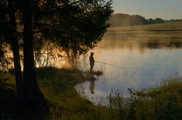 a fisherman on a wooded lake in the fog