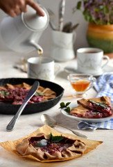 sweet Galette with plums and basil on a white table