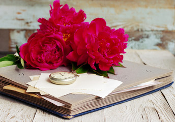 Bouquet of pink peonies, old photo album, old empty photographs and a pocket watch close up
