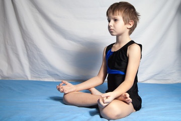 The young boy practices yoga