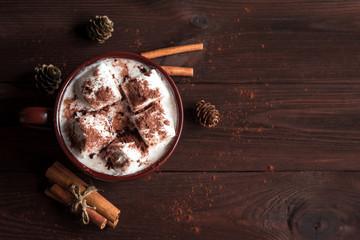 Hot chocolate in a mug, marshmallows, cinnamon sticks and fir cones, top view, flat lay