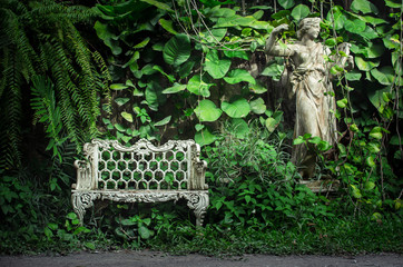 white europe style bench against forest back ground with a statu