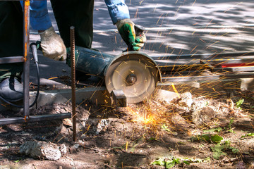 worker sawing the pipe with a grinder