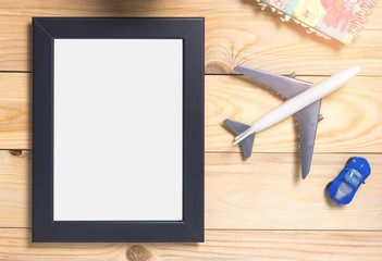 Blank Travel Picture frame on wooden table. Photo frame for vacation memories. Photo frame with blank space for pictures.