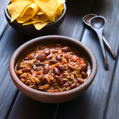 Rustic bowl of chili con carne with tortilla chips in the back, photographed with natural light (Selective Focus, Focus in the middle of the chili)