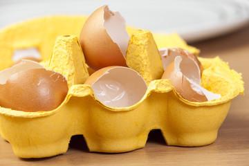 Yellow egg box full of broken egg shells