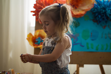 the little girl in the painting process, at the easel