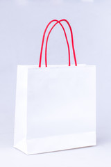 elegant white paper shopping bag with red handle