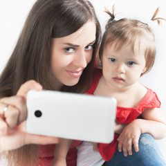 Funny baby and mother make selfie on mobile phone