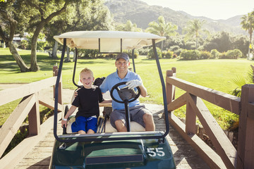 Father and son golfing together on a Summer day riding in a golf cart together