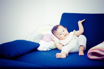 青いソファーに座っている赤ちゃん