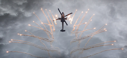 Silhouette of an attack helicopter firing flares