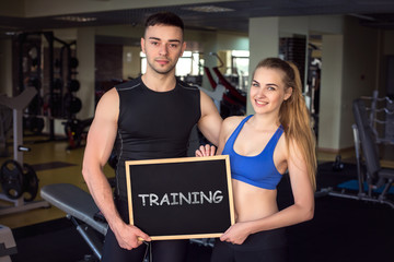 Athletic man and attractive girl  with a board in their hands an