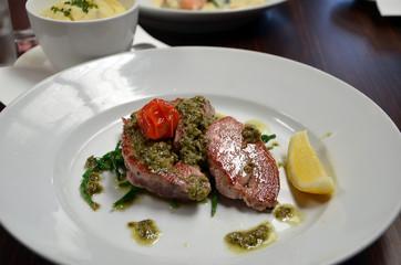 detail photography of tuna fish with capari and lemon in restaurant