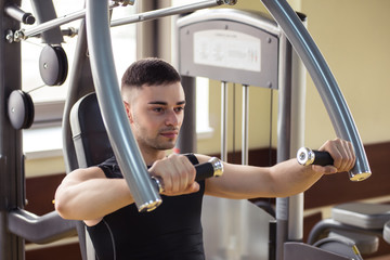 man does sports exercises in the gym