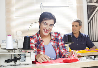 Happy Worker Sitting At Workbench In Sewing Factory