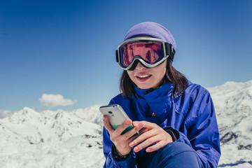 Skier woman look up in smart phone