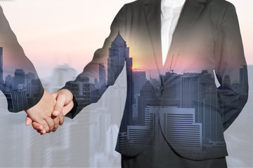 Double exposure of business women handshake, cityscape and sunset at evening as Commitment concept.