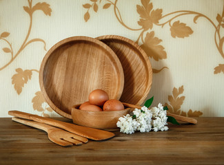 Wooden Plates,Kitchen Equipment.Eggs,White Branch of Lilac.Wooden Table.Floral Background.