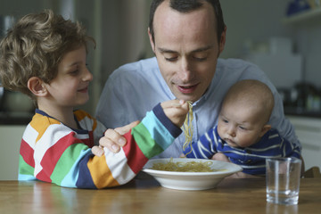 Son feeding noodles to father carrying son at home
