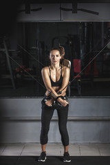 Full length portrait of woman exercising at gym