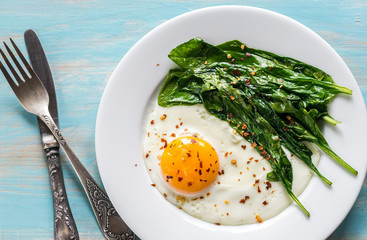 Photo sur Aluminium Ouf Fried egg with spinach on the wooden table